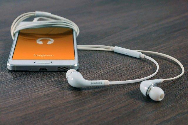 mobilní telefon se sluchátky na stole