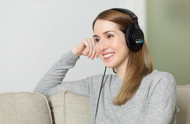 žena poslouchající hudbu ze sluchátek